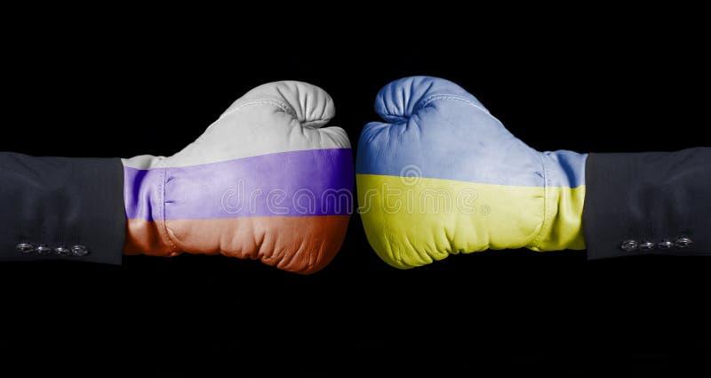 Boxninghandskar med ryss och den ukrainska flaggan Ryssland kontra Ukraina begrepp royaltyfria bilder