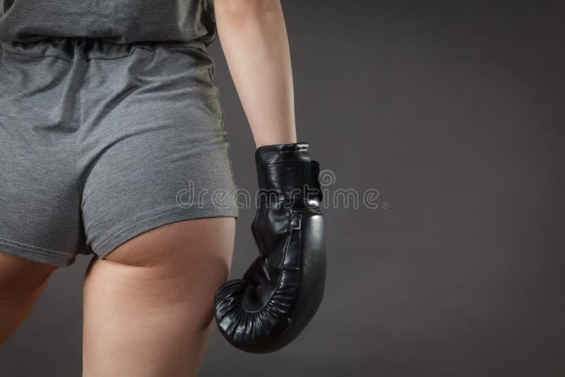 boxninghandskar som ser den allvarliga slitage kvinnan royaltyfri foto