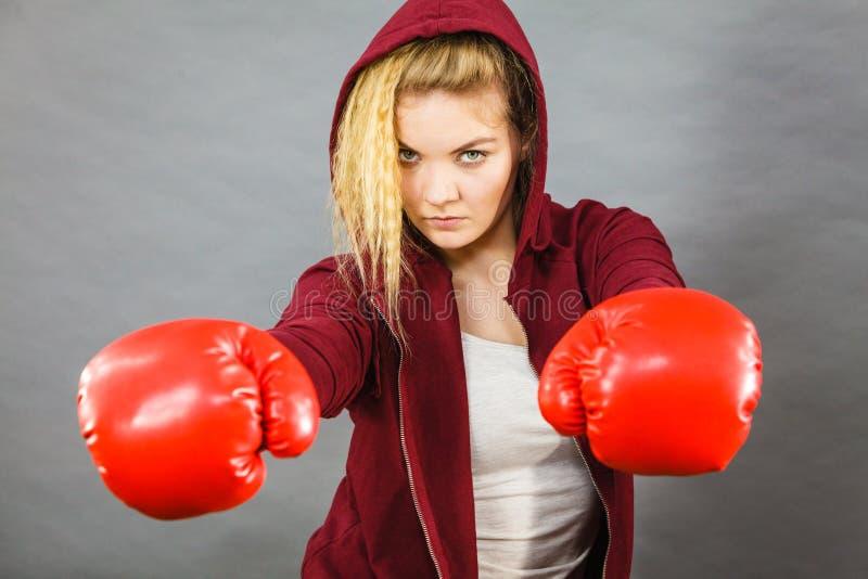 boxninghandskar som ser den allvarliga slitage kvinnan royaltyfri fotografi