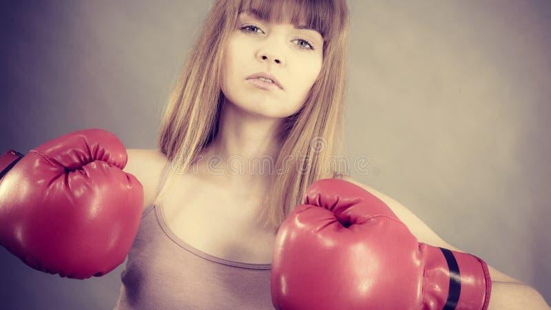 boxninghandskar som ser den allvarliga slitage kvinnan arkivbilder