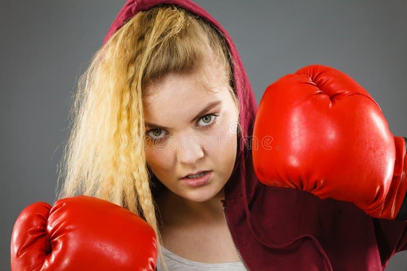 boxninghandskar som ser den allvarliga slitage kvinnan royaltyfria bilder