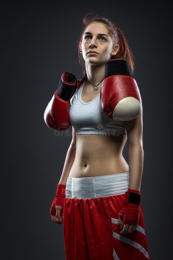 Boxningkvinnaanseende i klänningboxning, boxninghandskar på hans skuldra royaltyfri foto