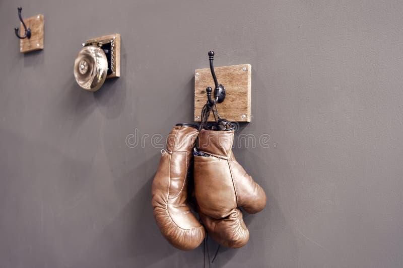 Boxningskola Sista munhuggas Tappningboxninghandskar h?nger p? krokv?ggbakgrund Boxninghandskar och cirkelklocka boxas royaltyfri bild