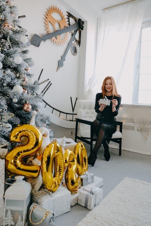 Boxtag Weihnachtsgeschenkideen für Frauen Ein Rotkopfmädchen in schwarzem Abendkleid Unpack Geschenke bei Weihnachtsbaum zu Hause stockfotografie