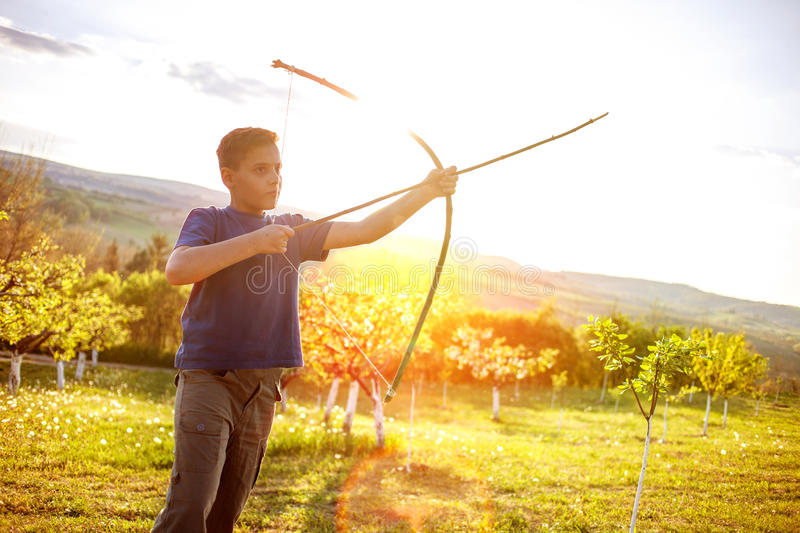 Boy aiming home-made wooden bow outdoors. Young boy with bow and arrow in the field stock photo