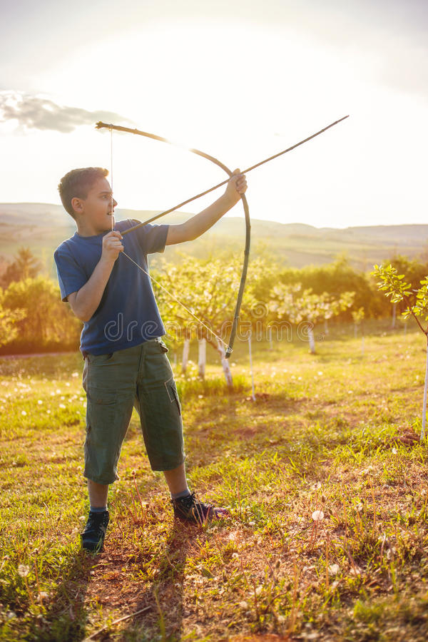 Boy aiming home-made wooden bow outdoors. Young boy with bow and arrow in the field royalty free stock images