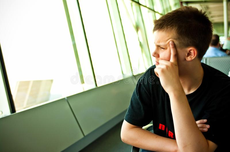 Boy in airport lounge. Portrait of a teenage boy sitting in an airport lounge looking out of the windows stock photo