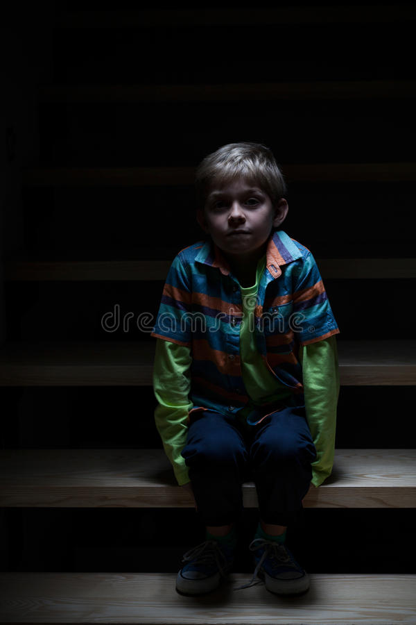 Boy alone on stairs at night stock photo