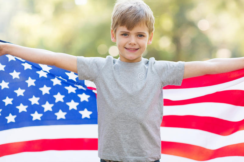 Boy american flag. Portrait of cute little boy holding american flag outdoors stock image