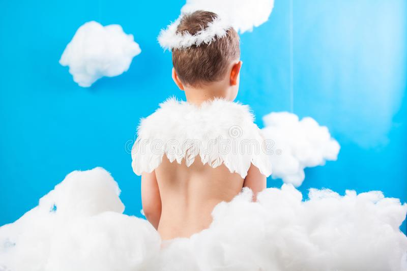 Boy angel sitting in the clouds stock image