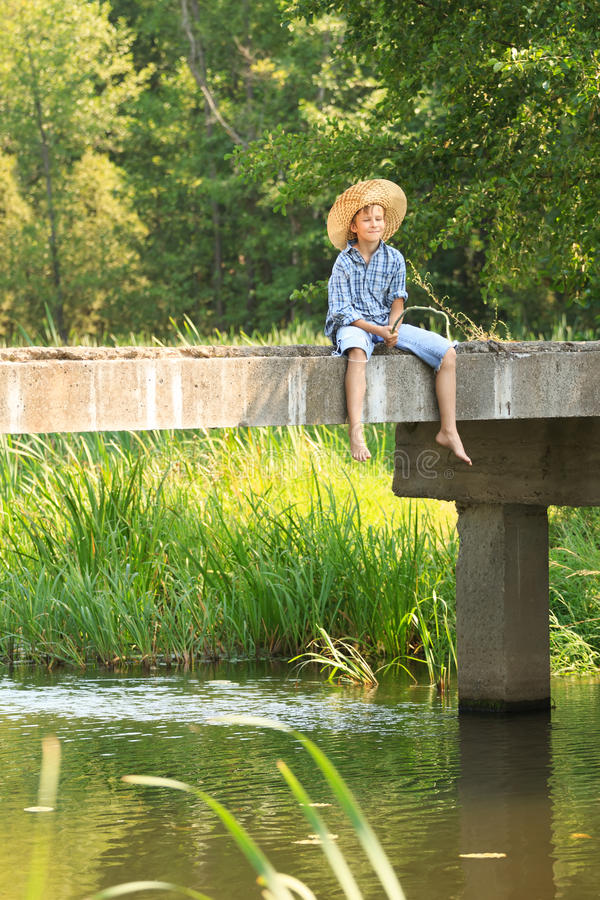Boy during angling with rod on bridge royalty free stock photos