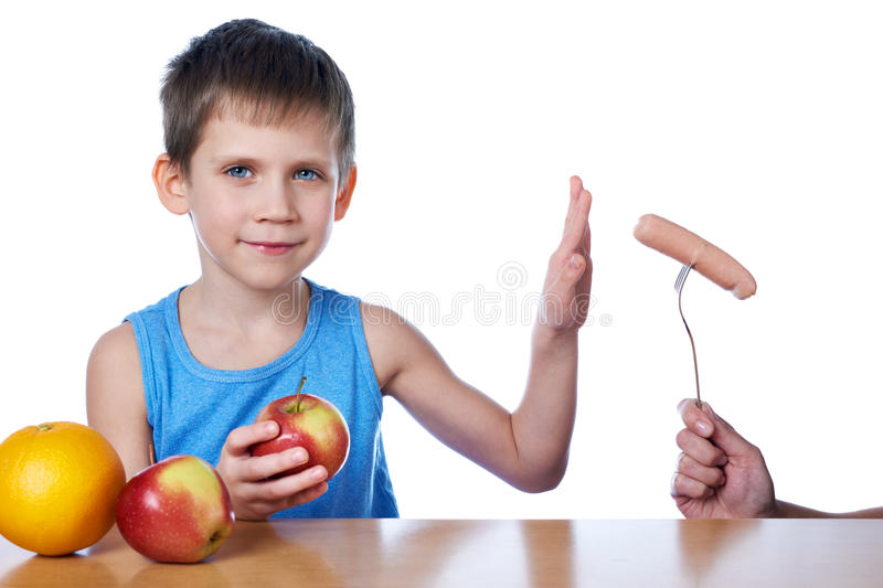 Boy with apples and orange against harmful sausage. Isolated royalty free stock photo