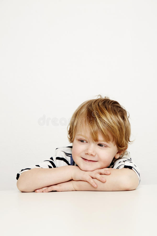 Boy with arms folded. Boy leaning on folded arms in studio, smiling stock photography