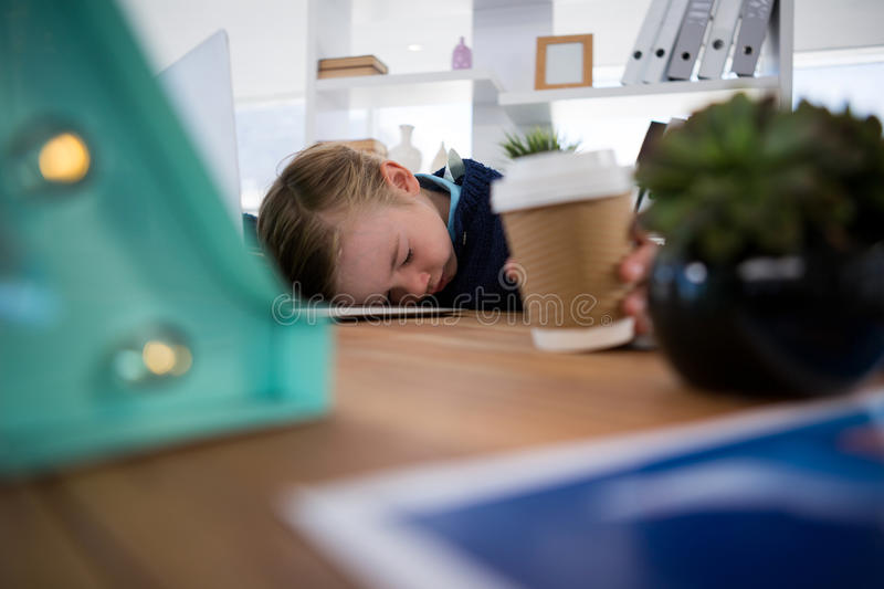Boy as business executive sleeping while holding coffee cup royalty free stock image