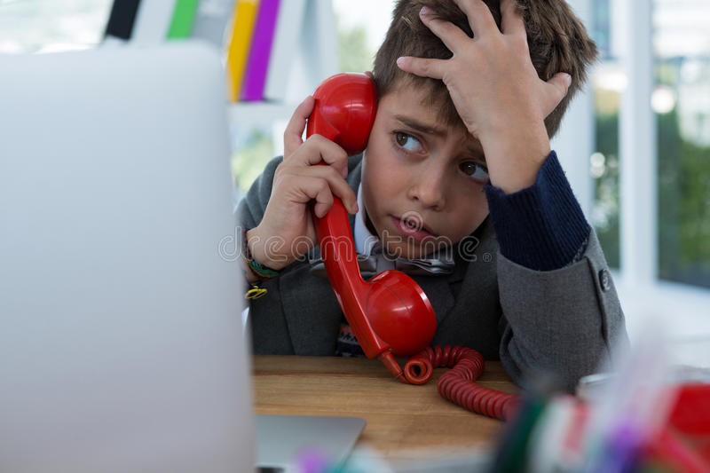 Boy as business executive talking on phone royalty free stock photos
