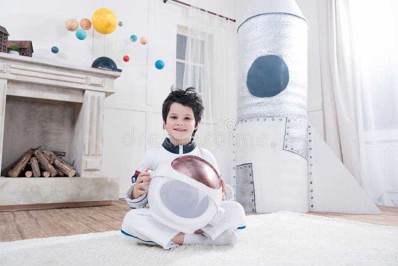 Boy in astronaut costume holding helmet, toy rocket behind royalty free stock images