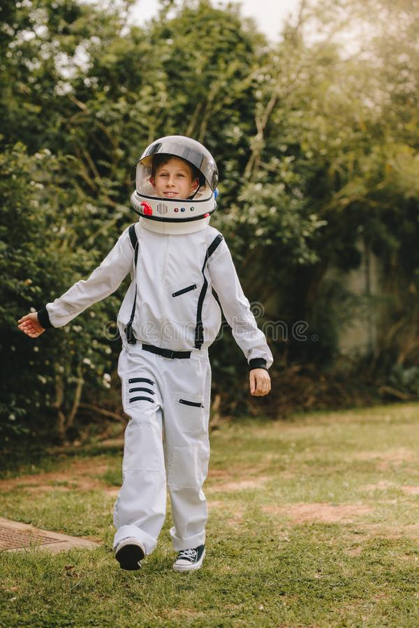 Boy in an astronaut suit playing outside. Small boy in an astronaut suit playing outside. Kid pretending to be an astronaut stock photography