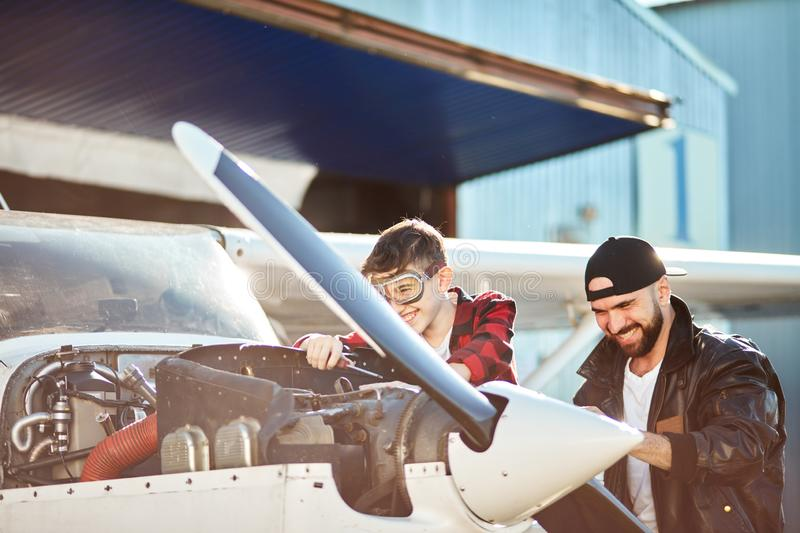 Boy in aviator glasses and man in pilot jacket laughing together at jokes royalty free stock image