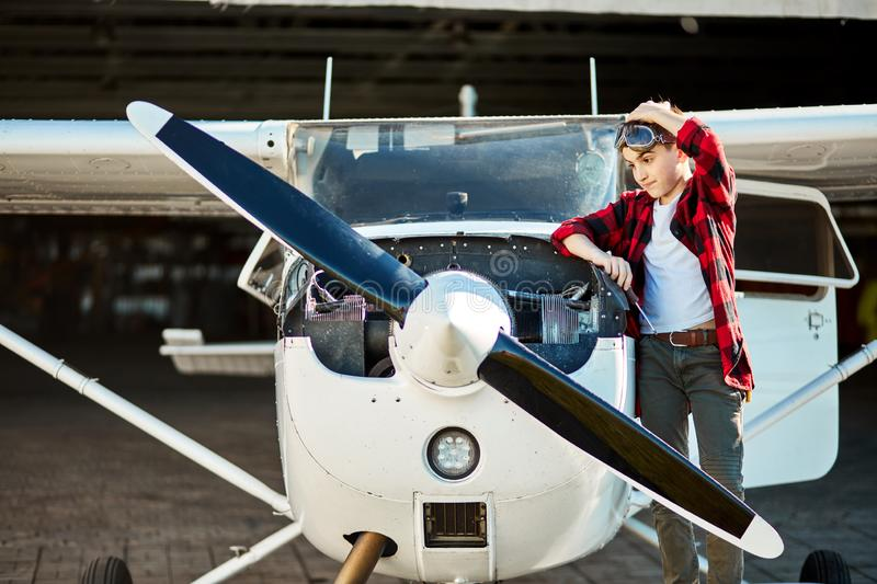 Boy in aviator glasses stands beside small white propeller airplane royalty free stock images