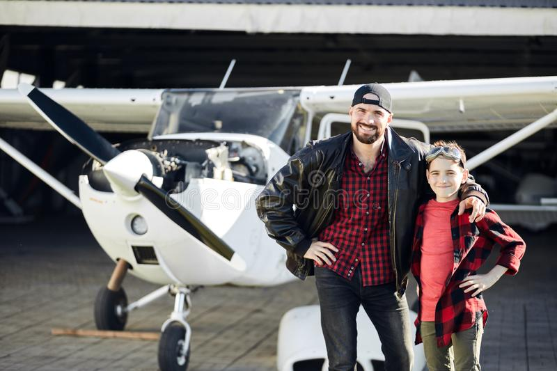 Boy in aviator glasses stands with his dad, wants to be a pilot too royalty free stock photography