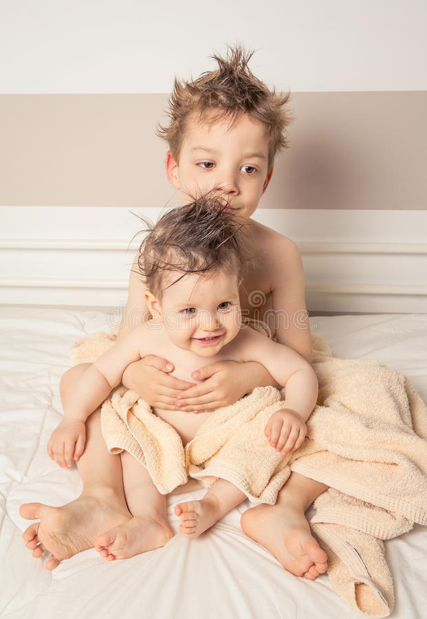Boy and baby with wet hair under towels over a bed. Portrait of sweet boy and little girl with wet hair under the towels sitting in a bed after bath stock images