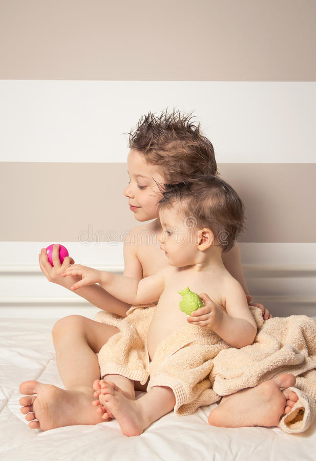 Boy and baby with wet hair under towels playing. Portrait of sweet boy and little girl with wet hair under the towels playing over a bed after bath royalty free stock images