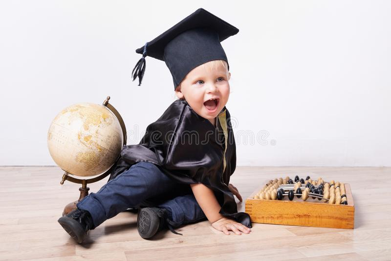 A boy in a bachelor or master suit with a globe and abacus on a light background. Early development, education, science, early royalty free stock photography