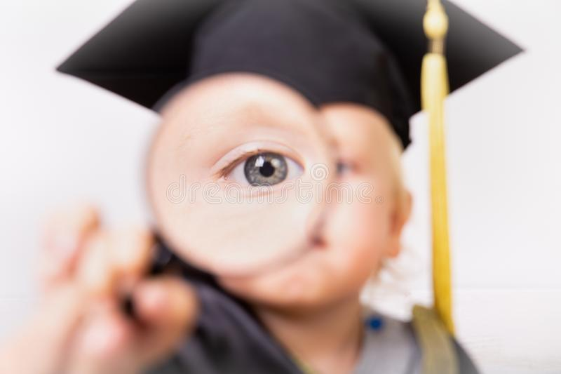 A boy in a bachelor or master suit looks through a magnifying glass. big children`s eye close-up. Early development, education, royalty free stock photos