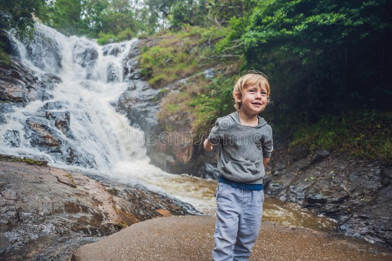 Boy in the background of beautiful cascading Datanla waterfall In the mountain town Dalat, Vietnam.  royalty free stock photography