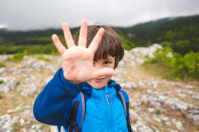 A boy with a backpack climbed to the top of the mountain and gives five royalty free stock images