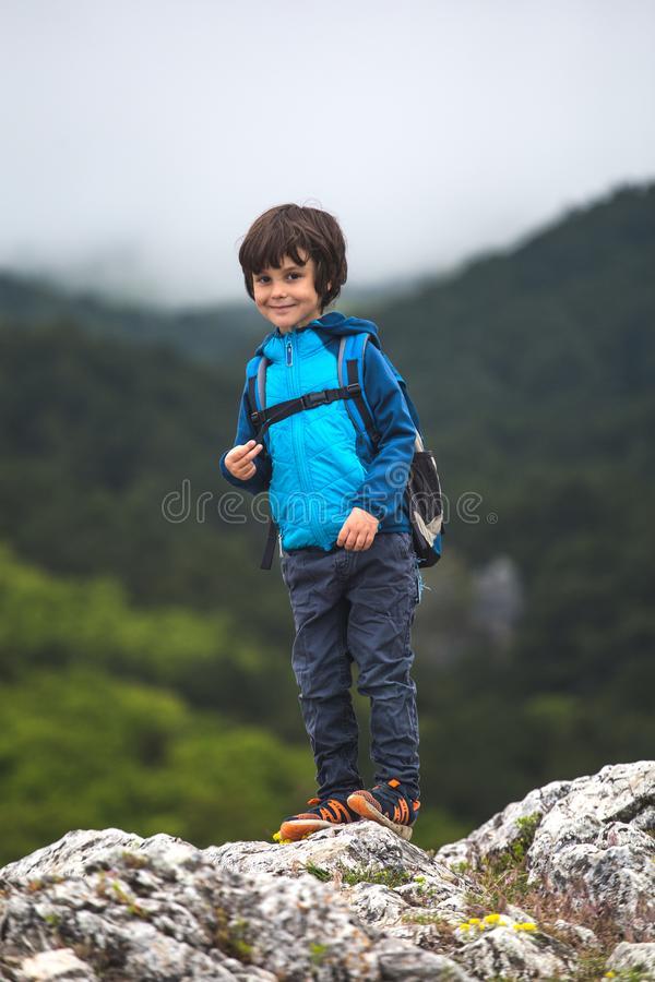 A boy with a backpack stands on top of a mountain stock photo