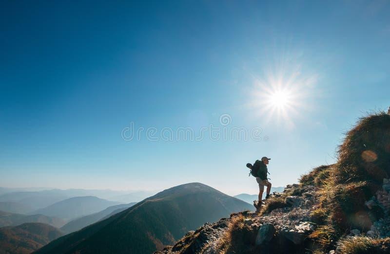 Boy backpacker traveler walk up on mountain top in contrast sun. Light royalty free stock photo