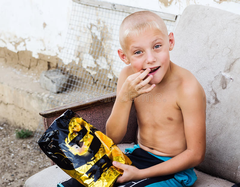 Download Boy With A Bag Of Chips In The Yard Of The Rural House Stock Photo - Image: 83710207
