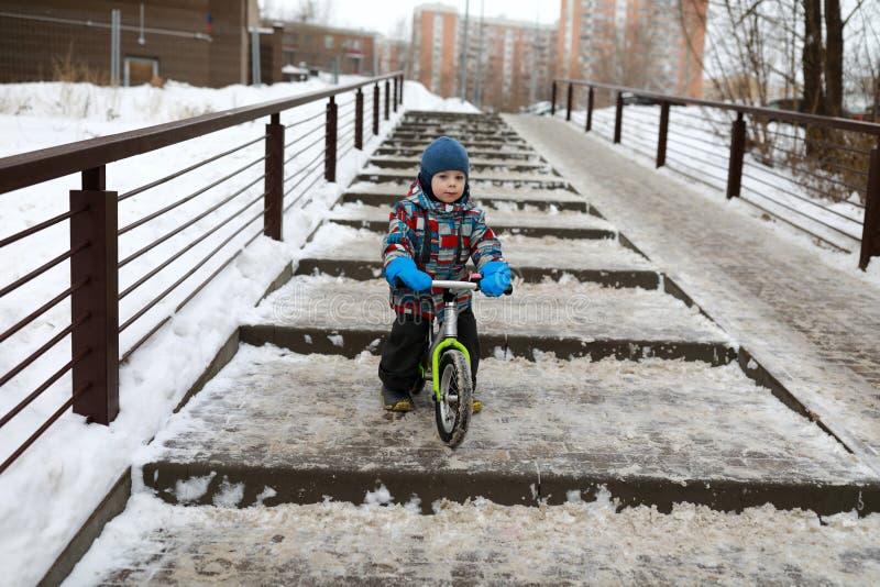 Boy on balance bike in winter stock photography