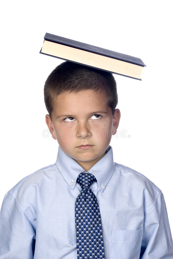 Boy balancing book on head royalty free stock photography