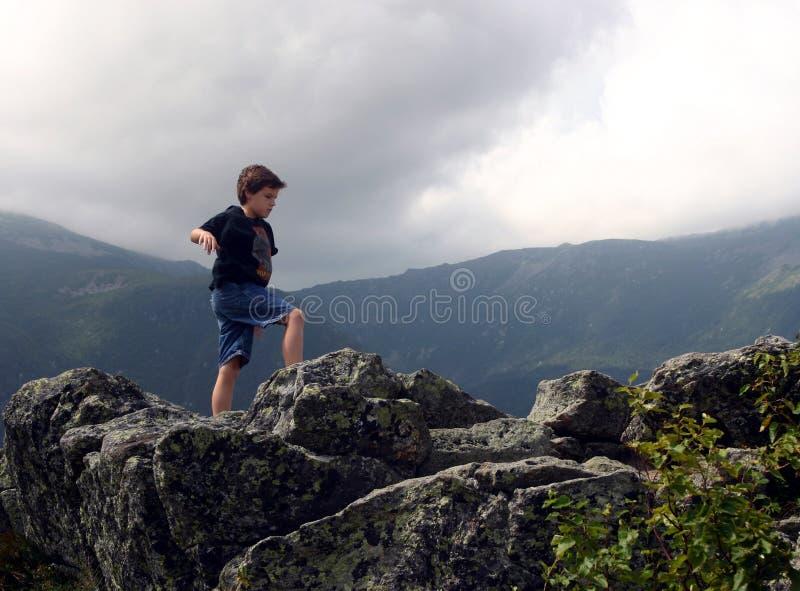 Download Boy Balancing on Rocks stock photo. Image of black, clouds - 5818304