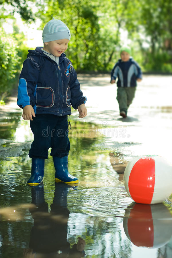 Boy with ball. In the puddle stock images