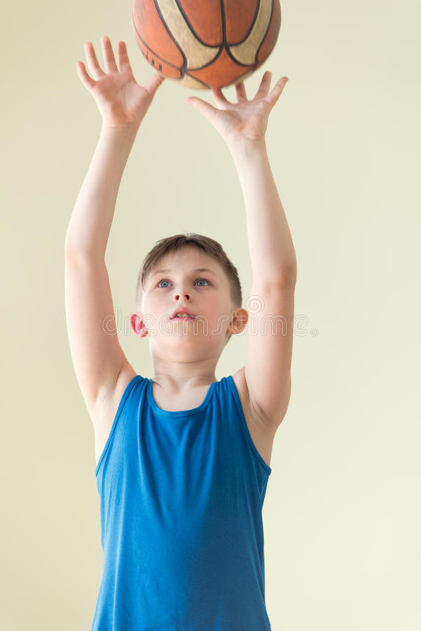 A boy with the ball. A caucasian boy in blue shirt holding backet ball royalty free stock photos