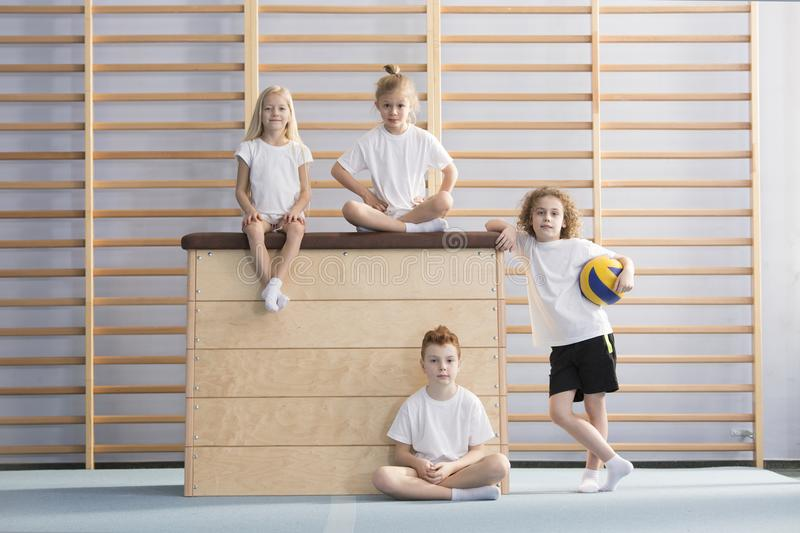 Smiling children on wooden box stock images