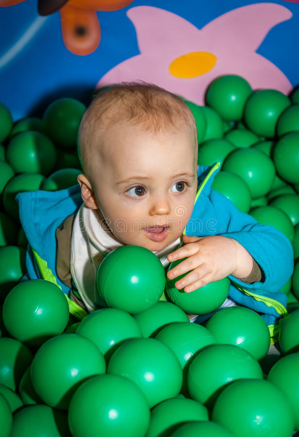 Boy among balls. Little boy having fun in an indoor playground in an activity centre stock photography