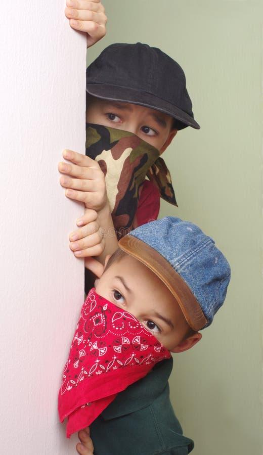 Boy bandits sneaking around corner royalty free stock image