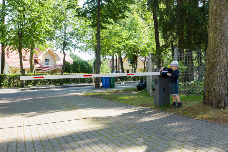 Boy and barrier. The little boy operates a barrier and blocks the road stock images