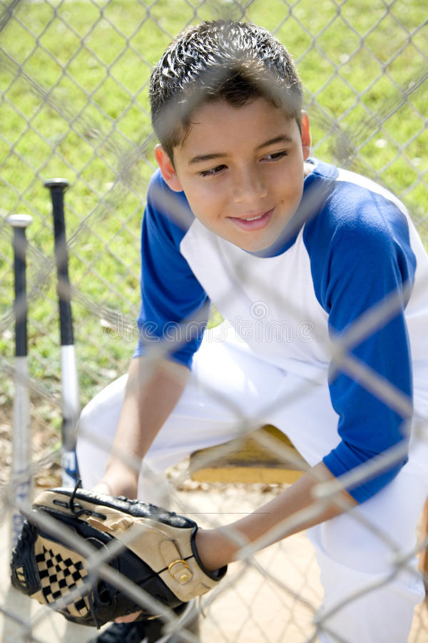 Boy in baseball gear sitting on a bench stock photography