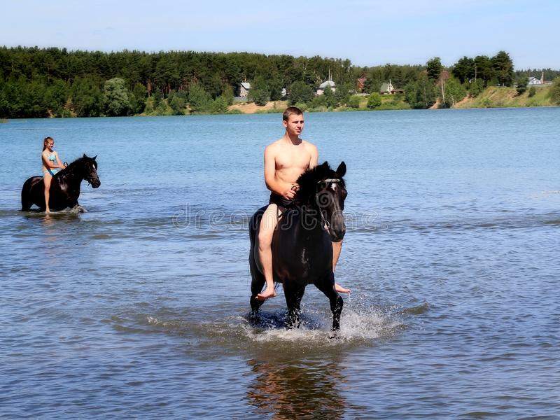 Boy bathe horse in the lake. Equestrian Sports Club brought horses to bathe in the lake. Russia. Moscow region. Schelkovsky district royalty free stock photo