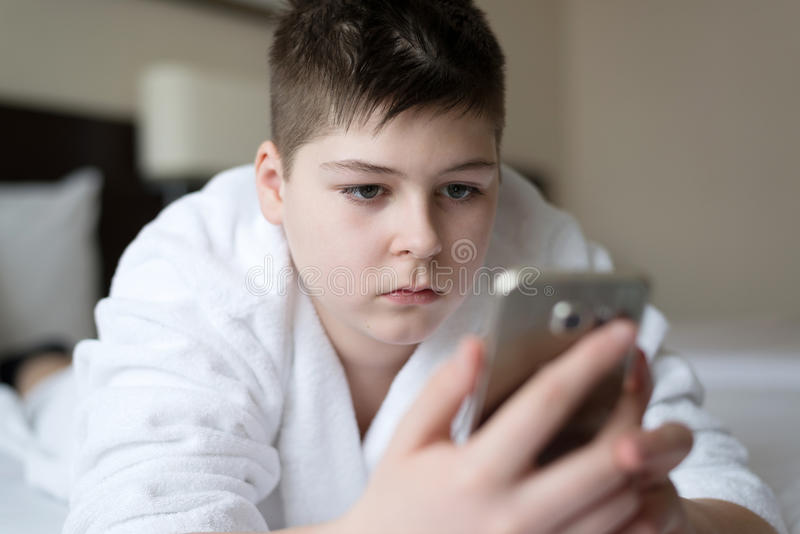 Boy in bathrobe writes sms on phone in hotel room royalty free stock images