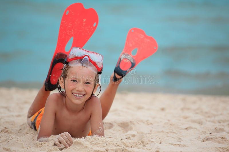 Boy on beach with flippers. Happy boy lying on beach with snorkeling face mask and flippers, sea in background stock image