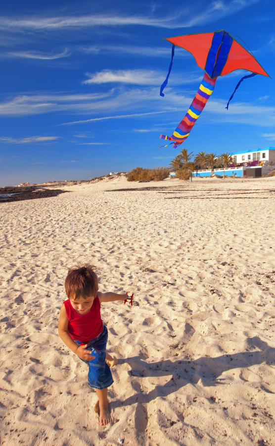 Boy on a beach with a kite royalty free stock images