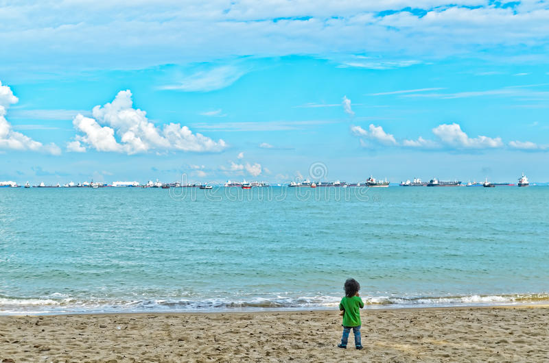 Boy on beach looking at sea royalty free stock photos