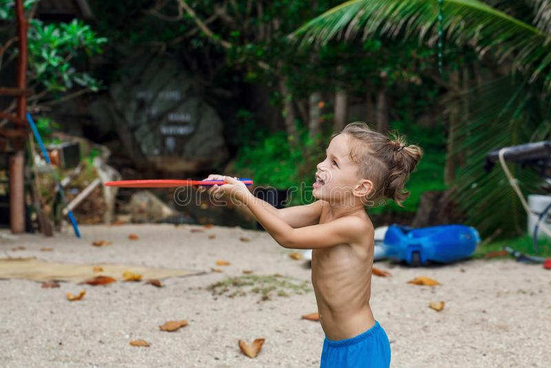 Boy on the beach playing beach tennis stock image