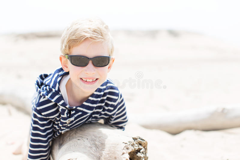 Boy at the beach. Smiling positive boy in sunglasses enjoying warm weather at the beach in california stock image